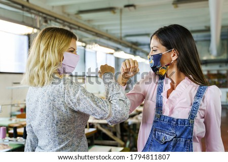 Two women greeting at work during covid-19 pandemic - Female friends workers elbow bump wearing protective masks in factory - front view in bright day - Real people new normal social distance concept