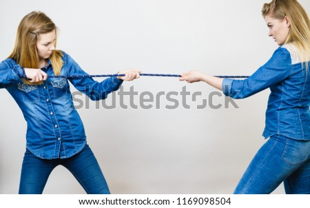 Two women having argue pulling rope being mad at each other. Bad rivalry relationship. #1169098504