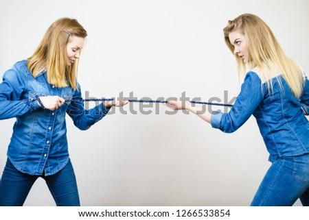 Two women having argue pulling rope being mad at each other. Bad rivalry relationship. #1266533854