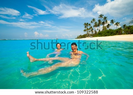 Two women having fun in the ocean on a tropical coast