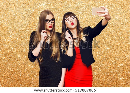 Two women having  great time together, making self portrait , use carnival funny paper glasses, wearing  elegant evening dress. Friends celebrating  new year or birthday party.