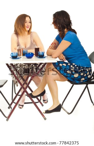 Two women having happy conversation and sitting at table in a cafe shop isolate don white background