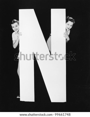 Two women hiding behind huge letter N
