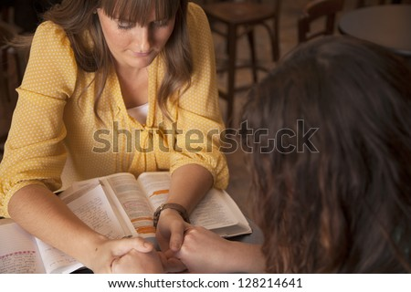 Two women hold hands and pray as they study the bible.