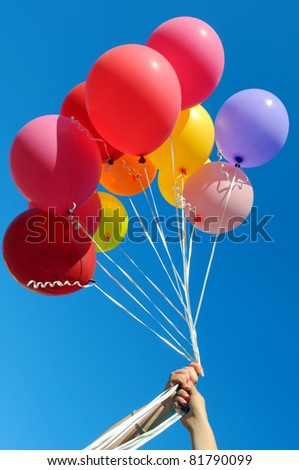 two women holding multicolored balloons in the city festival