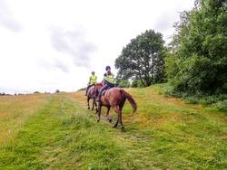 Two women horse riding on Chorleywood Common, Hertfordshire