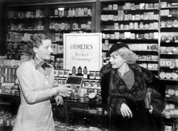 Two women in a drug store looking at each other