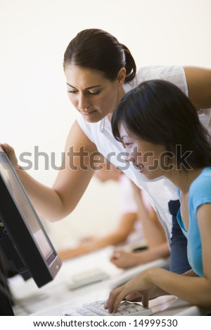 Two women in computer room where one is assisting the other