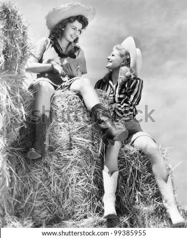 Two women in cowboy hats sitting on a haystack Zdjęcia stock ©