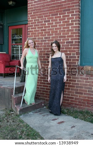 Two women in formal dresses by a loading dock