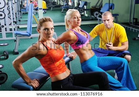 two women in gym exercising...