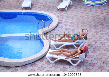 Two women in hats while relaxing in deck chair near the pool. Sunbathe after water procedures. Inner courtyard hotel. View from above #1043007823