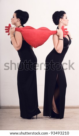 Two women in long dresses pulled the pillow in the shape of the heart in different directions. The conflict.