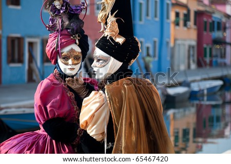 Two women in mask on Venetian carnival. Burano island, Venice, Italy.
