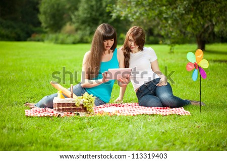 Two women in the park on a picnic and Tablet PC