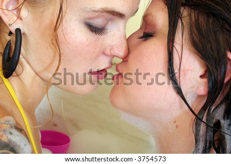 Two women kissing in bathtub