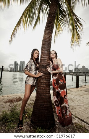 Two women leaning against a palm tree