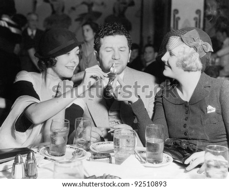 Two women lighting a cigarette for a man
