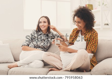 Two women listening music online on smartphone and sharing earphones sitting on couch at home, copy space