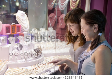 Two women looking jewelry counter at shop