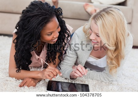Two women lying down on the floor are looking at each other with a tablet in front of them
