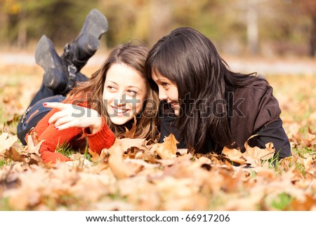 Two women lying in the autumn park leaves