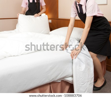 Two women maid making bed in hotel room