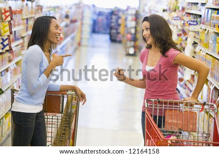Two women meeting and chatting in supermarket aisle
