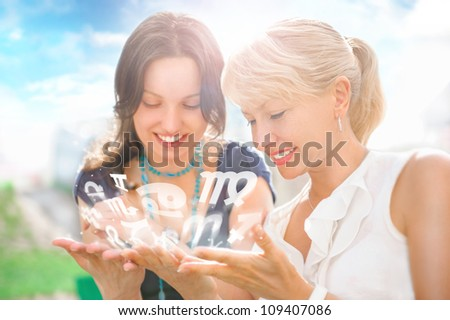 Two women mother and daughter sitting at summer park and having fun while discussing horoscope and different zodiac symbols appearing from their hands