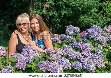 Two women of different generations standing near flowers hydrangeas. Mother and daughter. Grandmother and granddaughter.