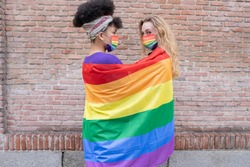 two women of mixed race wrapped in a gay pride flag, with rainbow face masks.