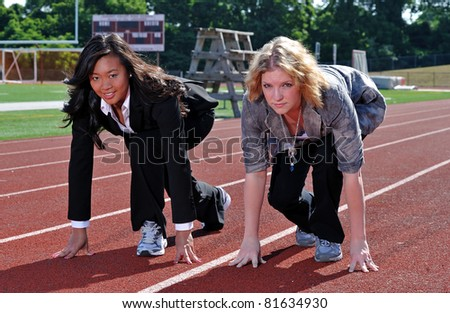 Two women - one Asian and one Caucasian - in business attire in a starting pose for a race on the track. Symbolizing competition in business