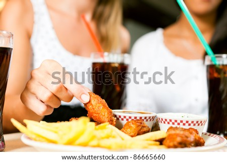 Two women - one is African American - eating chicken wings and drinking soda in a fast food diner; focus on the meal
