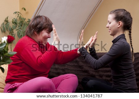 Two women, one of them disabled, making rhythm exercises