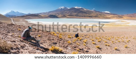Two women outdoor photographers taking photos at Tuyajto Lagoon, awe turquoise color at Atacama Desert. An arid landscape full of salt flats and lakes with beautiful volcanic scenery on a sunny day #1409996660