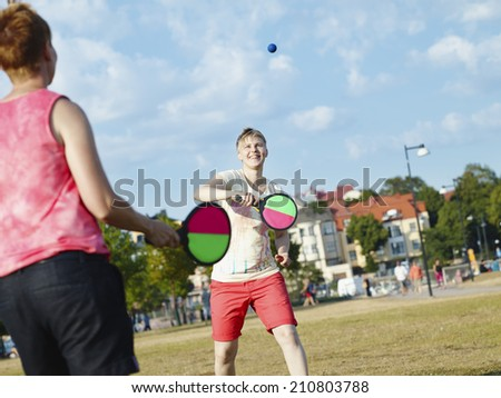 Two women play summer game in the park in the afternoon sunlight, city on background
