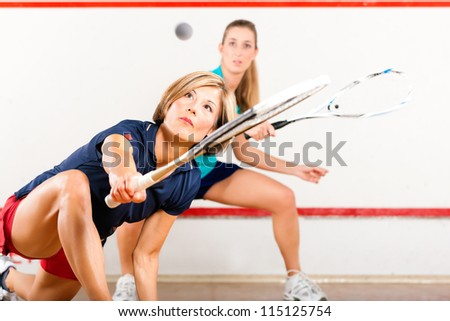 Two women playing squash as racket sport in gym, it might be a competition ストックフォト ©