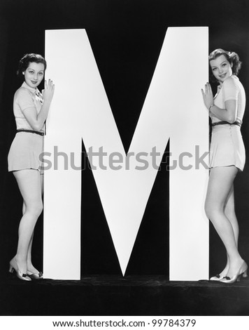 Two women posing with huge letter M