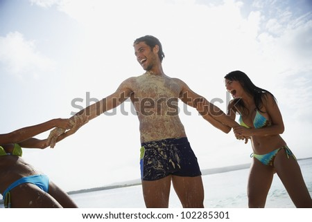 Two women pulling on man's arms