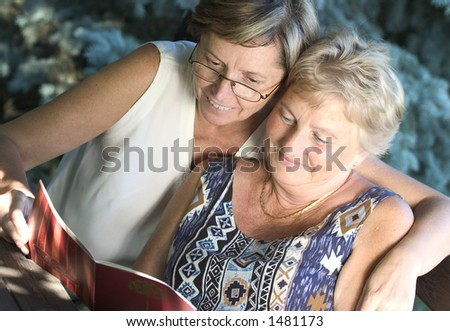 Two women reading a book together.
