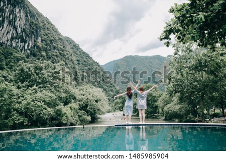 Two women relaxing by the pool breathing fresh air in the morning with mountain and river at Vang Vieng, Laos. Concept relax vacation