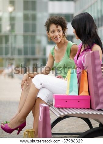 two women relaxing on bench after shopping. Vertical shape, full length, copy space