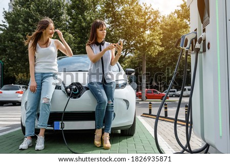 Two women's best friends are sitting on the electric car until one of them is using her smartphone to pay for charging her electric car. Mobile payment concept. Eco friendly electric car technology