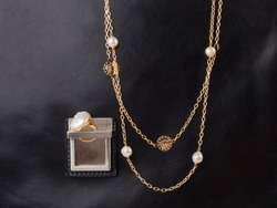 Two women`s gold necklaces and baroque pearl ring on male black leather case background. Close-up shot