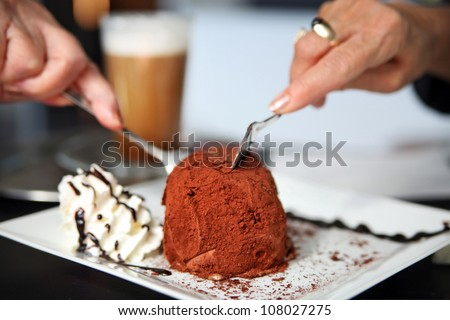 Two women's hands reach to slice cocoa powder topped cake on plate