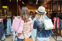 Two women shopping as customers in front of a retail boutique