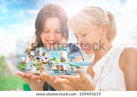 Two women sitting at park and using virtual interface to watch video or pictures