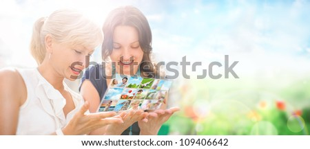 Two women sitting at park and using virtual interface to watch video or pictures - stock photo
