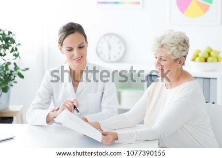 Two women sitting in a dietician's office and talking about a new diet plan. Healthy living concept