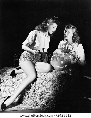 Two women sitting on a bale of hay carving a pumpkin